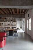 Loft apartment with rustic wooden ceiling; contemporary table with retro chairs and partition bookcase in background