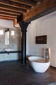 Freistehende Designer-Badewanne mit Standarmatur auf Natursteinfliesen, vor schwarzer Metallstütze