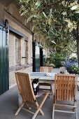 Table, wooden chairs, olive tree and cat on terrace outside industrial loft apartment with brick facade