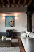 Pale grey sofa, cubic coffee table and large Renaissance portrait on wall in rustic loft apartment