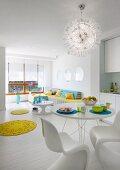 Offener Wohnraum in Weiss, Essplatz mit Klassiker Schalenstühlen unter strahlenförmiger Pendelleuchte, gelbe, runde Teppiche als Farbtupfer