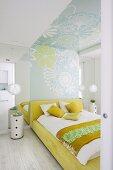 Blick durch offene Tür auf Doppelbett mit Bettwäsche in weissen und gelben Farbtönen, an Wand und Decke Tapete mit Blumenmuster