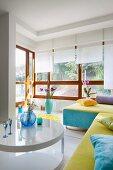 Weisser Couchtisch vor Couch mit blau-gelbem Bezug, im Hintergrund Erkerbereich mit Holzfenstern und weissen Rollos