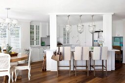 Upholstered bar stool at counter with white wooden frame below glass pendant lamps in open-plan kitchen
