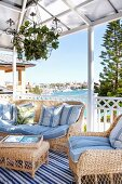 Pale wicker sofa set with pale blue cushions on roofed terrace with view of sea shore in background