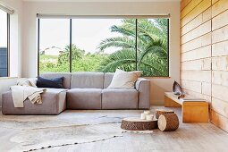 Comfortable seating area with sofa next to panoramic window, animal-skin rug on wooden floor, slices of tree trunk used as low coffee tables and bench against wood-clad wall