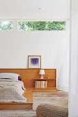 Futon on wooden platform with bedside lamp on shelf integrated into wooden headboard below ribbon window
