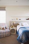 Kinderzimmer in hellen Farben mit Bett, modernem Nachttisch und Sessel