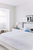 Weisse Tagesdecke auf Doppelbett in modernem Schlafzimmer
