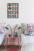 Plexiglas Nachttisch mit mehrarmiger Tischleuchte zwischen Einzelbetten, vor geweisselter Ziegelwand mit gerahmtem Poster