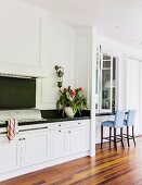 Kitchen counter with dark worksurface, white base units and seating area to one side on elegant veranda with wooden floor