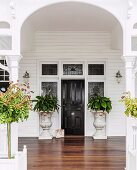 Veranda with white-painted archway and wooden floor leading to elegant front door flanked by antique planters
