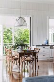 Ornate, Colonial-style wooden chairs below elegant pendant lamps in dining area in front of French windows
