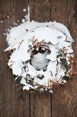 DIY-Kranz aus Efeuranken mit Schneeresten auf Bretterwand