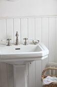 Standwaschbecken mit Vintage Armatur vor halbhoher Holzvertäfelung