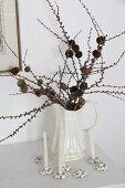 Lärchenzweige mit kleinen Zapfen in Porzellankrug und Kerzenhalter in Blütenform