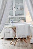 Blick durch drapierten Vorhang auf Holzbügelbrett mit Spitzendecke, dahinter ein weisse Anrichte