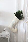 Weisser Nikolausstiefel mit Zweigen an drapiertem Vorhang, daneben eine Vintage Laterne