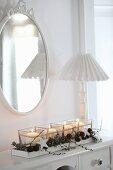 Windlichter mit adventlicher Deko aus Zapfen und weissen Holzsternen in länglichem Holztablett, Leuchte mit Plisseeschirm und Ovalspiegel