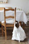 Umhängetasche aus Spitzenstoff an Holzstuhllehne und Tisch mit weisser Spitzentischdecke