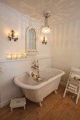 Romantisches Badezimmer mit Kristalllüster und Kerzenlicht über freistehender Klauenwanne