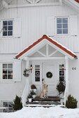 Weisses Landhaus mit Holzverschalung und Windfang, Hund vor Hauseingang