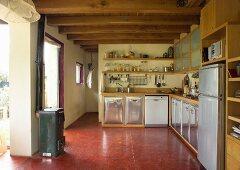 Offene Küche mit rotem Fussboden, Unterschränke mit gewölbter Front aus Edelstahl und Holz Arbeitsplatte, gegenüber Kaminofen neben Durchgang