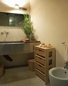 Half-height pale wooden shelves with storage baskets next to trough-style sink and vase of leaves on counter in modern bathroom