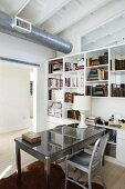 Grey desk and table next to white shelving below ventilation duct running below wooden ceiling