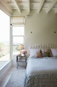Bed with upholstered headboard and ruffled bedspread in bedroom with white wooden ceiling