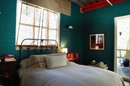 Bed with vintage metal frame below window and table lamp on red bedside cabinet in simple bedroom with brick walls painted dark green