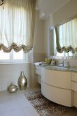 Designer bathroom with elegant curved washstand, shiny vases and draped gathered curtains