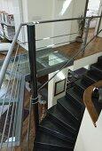 Gewendelte schwarze Metalltreppe in modernem Wohnraum mit Galerie