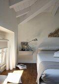 Minimalistisches Nachtkästchen an Wand montiert neben Bett im Dachzimmer