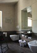 Modernes Bad mit dunklen Bodenfliesen und in Brüstungshöhe an Wand, Waschtisch in massgefertigtem Schrankeinbau integriert