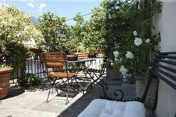 Sonnige Terrasse mit Tisch und Stühlen, Blumentöpfe auf Natursteinboden und Vintage Sitzbank an Hauswand