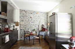 Küche mit Edelstahlfront und Kühlschrankkombination, im Hintergrund Natursteinwand und Essplatz
