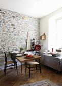 Set dining table against stone wall in modern kitchen