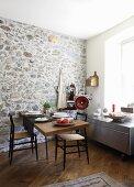 Gedeckter Essplatz vor Natursteinwand in moderner Küche