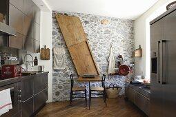 Edelstahlküche mit Kühlschrankkombination und Natursteinwand mit klappbarer vergrößerter Holztischplatte