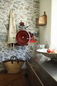 Kitchen base unit on castors, apron and retro slicing machine mounted on stone wall