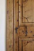Restaurierte rustikale Kassettentür mit traditionellem schmiedeeisernem Türgriff