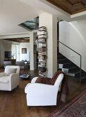 weiße Sessel in offenem Wohnraum, im Hintergrund Stahltreppenaufgang