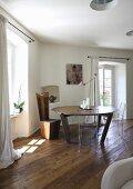 Moderner, runder Tisch und extravaganter Stuhl in Zimmerecke mit rustikalem Dielenboden