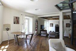 Essplatz mit rundem Tisch, im Hintergrund Loungebereich mit Sesseln in modernem, offenem renoviertem Wohnraum