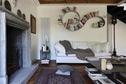 Geschwungenes Bücherregal, Bookworm, über weißem Polstersofa in Loungeecke mit offenem Kamin