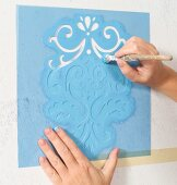 Stippling pale blue paint through a hand-crafted, ornamental stencil; hands holding paintbrush and stencil