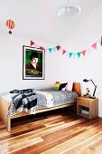 Bunting and film poster (Amélie) above solid-wood teenager's bed on parquet floor made of spotted gum wood native to Australia
