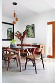 Poster and fifties-look sideboard in dining area with wooden chairs and wooden table with glass top