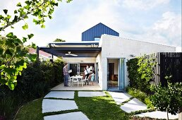 Large stepping stones in lawn leading to roofed terrace of Australian house